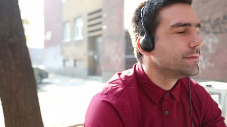 камедь : Close-up of a young man listening to music with headphones and chewing gum Стоковые видеозаписи