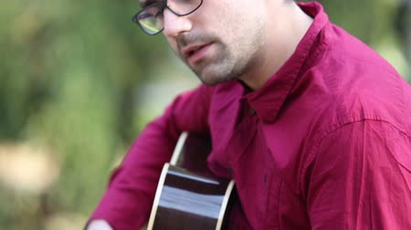 headstock : Close-up view of a young man playing the guitar and singing Stock Footage