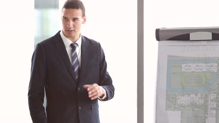 conferência : Handsome young businessman pointing at flipchart during presentation in conference room