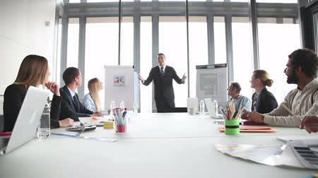 executivo : Smiling young businessman giving presentation to colleagues in conference room