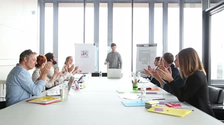 motive etmek : Young male advertising executive giving presentation in conference room, colleagues clapping