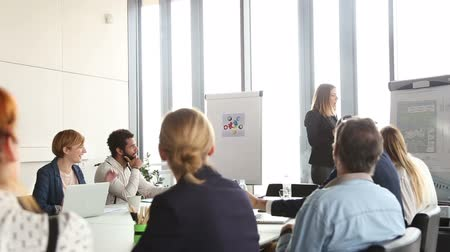 sala de reuniões : Beautiful young businesswoman giving presentation to colleagues using flipchart