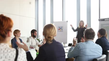 компания : Colleagues applauding to beautiful businesswoman after presentation in conference room