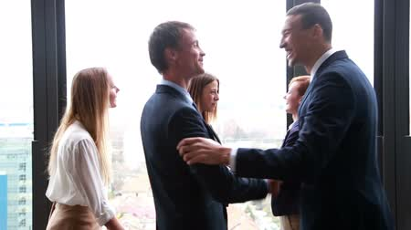 corporate : Young business people meet up with other colleagues and shake hands Stock Footage