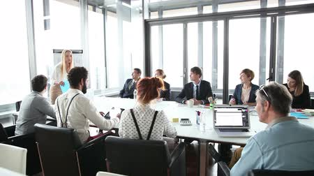 sitting room : Business people sitting at table while beautiful female colleague giving presentation in conference room, slow motion Stock Footage