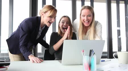 excitação : Close up of three beautiful smiling businesswoman with laptop in office, high-fiving and cheering