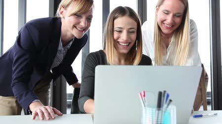 három ember : Close up of three beautiful smiling businesswoman with laptop in office, high-fiving and cheering