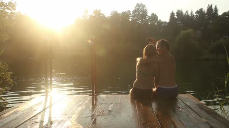 outside view : Back view of beautiful couple in love taking selfies and kissing while sitting on the dock by the Mreznica river at sunset Stock Footage