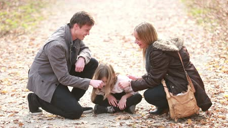 falar : Beautiful young family sitting on pathway and playing games, enjoying in park in autumn