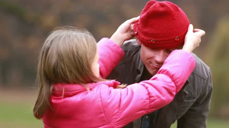 čepice : Close up of cute little girl putting her red cap on dads head