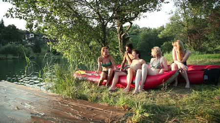 kıvırcık : Group of five young happy friends resting in nature after riding a canoe, talking and laughing by the river at sunset