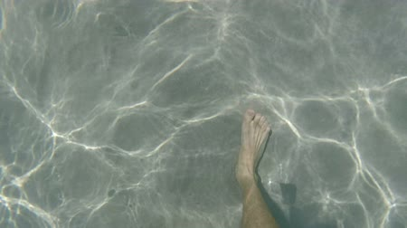 claro : View from above of mans feet walking under sea