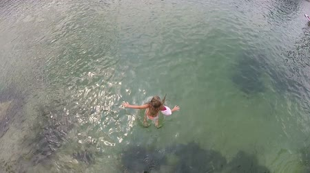 curativo : View from above of little girl jumping into river