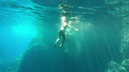cliff : Underwater shot of couple swimming and diving in cave Stock Footage