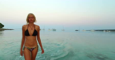 vista frontal : Front view of blonde woman getting out of the sea at Slatinica beach at Olib Island in Croatia