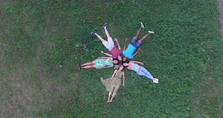 aşağı bakıyor : Aerial view of five happy friends forming a star shape lying in grass