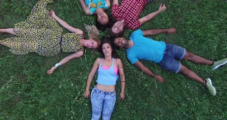 над : Close aerial view of five beautiful young friends forming a star shape lying in grass