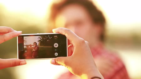 filmagens : View of a womans hand holding a mobile phone and taking pictures man at sunset, graded warmer. Stock Footage