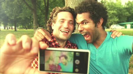гей : A close up of two young men taking a selfie in the park, graded warmer.
