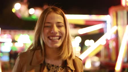 смеющийся : Close up of beautiful young woman laughing and waving at camera in amusement park Стоковые видеозаписи