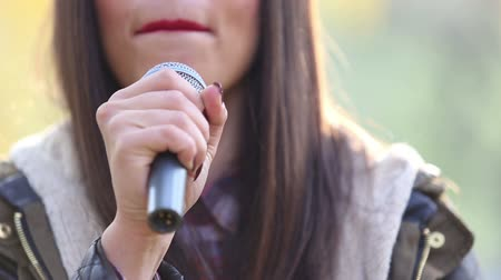 dış : Close-up of beautiful womans mouth with red lipstick, smiling and singing with microphone Stok Video