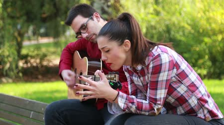 śpiew : Side view of beautiful young couple sitting on park bench, man playing guitar while woman singing Wideo