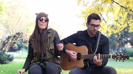 black yellow : Beautiful brunette woman singing while handsome man playing guitar sitting on park bench Stock Footage