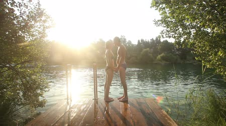 outside view : Young couple kissing and jumping into water from river dock at sunset Stock Footage