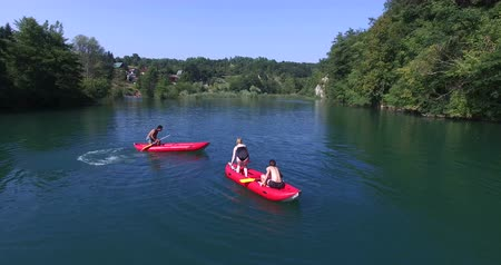 четыре человека : Aerial view of four young friends having fun in canoe and jumping into river on beautiful summer day