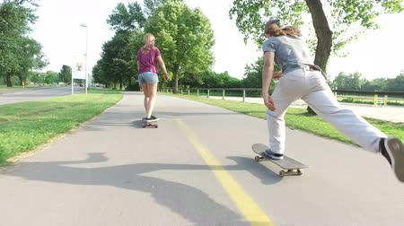 deskorolka : Three people having fun skateboarding on cycling pathway
