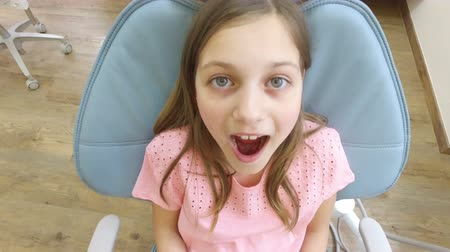 kinyit : Close up of beautiful little girl sitting in the dental chair with open mouth