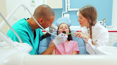 asistan : Happy little girl with female dentist and male surgeon giving thumbs up after dental check up Stok Video