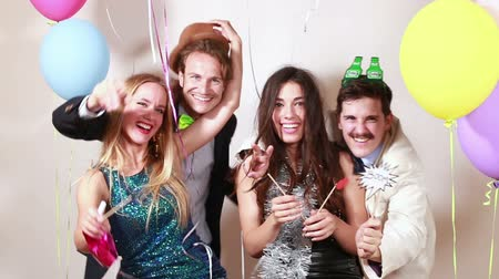 фото : Two happy couples having great time in party photo booth Стоковые видеозаписи