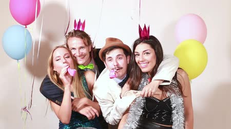 фото : Group of funny crazy friends having great time in party photo booth Стоковые видеозаписи
