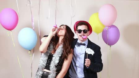 a party : Beautiful young couple blowing party horns in party photo booth