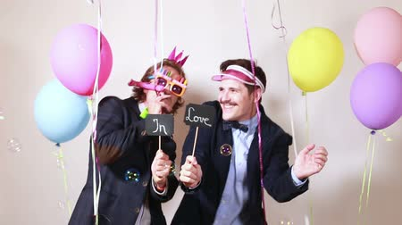 гей : Two male friends having fun dancing with boards in love in party photo booth