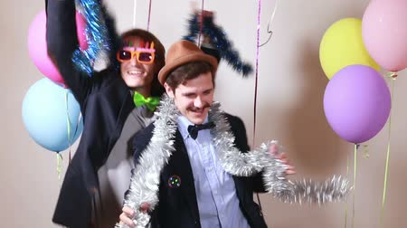 double happiness : Two male friends dancing and giving double high five in party photo booth