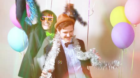 double happiness : Two male friends dancing and giving double high five in party photo booth, graded Stock Footage