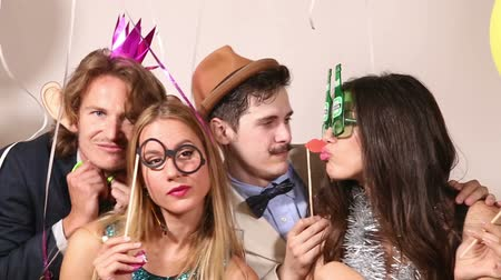 фото : Funny young couples playing with props in party photo booth