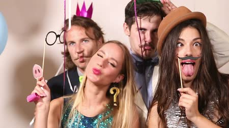 фото : Two beautiful couples playing with funny props in party photo booth