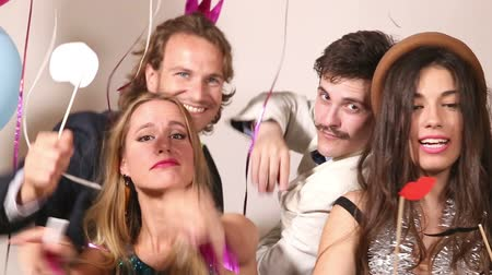 фото : Two beautiful girls and two handsome guys playing with props in party photo booth Стоковые видеозаписи