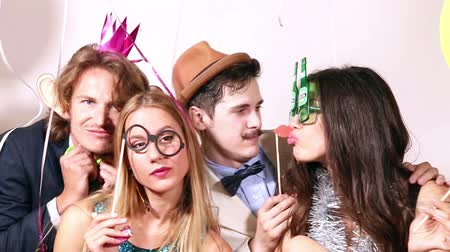 фото : Funny young couples playing with props in party photo booth, graded Стоковые видеозаписи