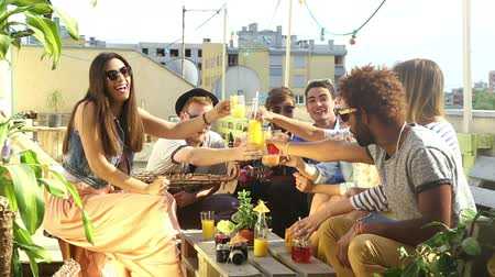 coquetel : Group of happy multi-ethnic friends looking at camera and toasting with cocktails at rooftop party on beautiful sunny day, graded