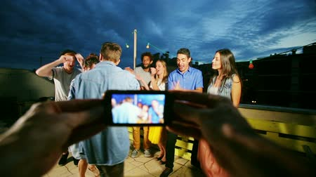 filmagens : View of hands holding phone and filming beautiful couple dancing in the middle and friends dancing around them, graded