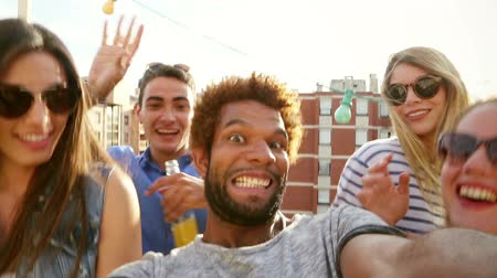 filmagens : Close up of smiling guy filming himself and cheerful friends at rooftop party on sunny day, graded