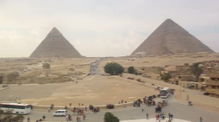 wielbłąd : View of tourists walking around Giza pyramids in Egypt