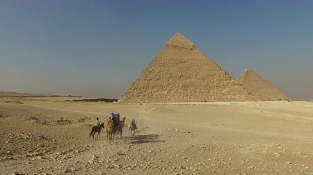 piramit : Tourists riding camels at Giza pyramids