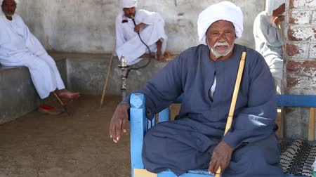 aswan : DARAW, EGYPT - 06 FEBRUARY 2016: Egyptian man in traditional clothing sitting on the bench Stock Footage