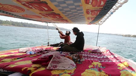 aswan : NILE, EGYPT - FEBRUARY 8, 2016: Local man and tourist sailing with felucca on Nile river Stock Footage