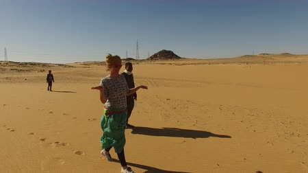 дюна : ASWAN, EGYPT - FEBRUARY 7, 2016: Happy woman walking in desert with nubian guide Стоковые видеозаписи